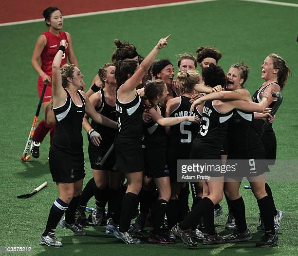 Michaela Curtis of New Zealand is congratulated by teamates after scoring the winning goal in extra time of the Girls Hockey Bronze Medal match...