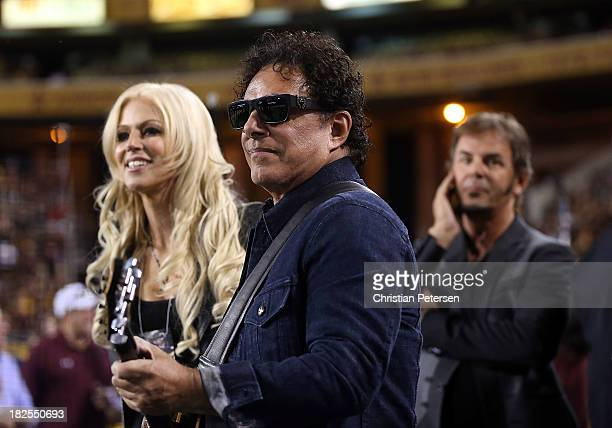 Michaele Salahi looks on as Neal Schon and Jonathan Cain of Journey prepare to perform the National Anthem at the college football game between the...
