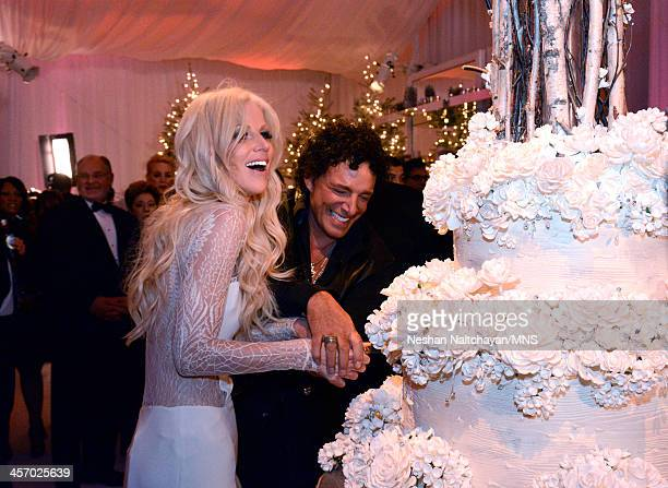 Michaele Schon and Neal Schon cut the cake by Sam Godfrey at their wedding at the Palace of Fine Arts on December 15 2013 in San Francisco California