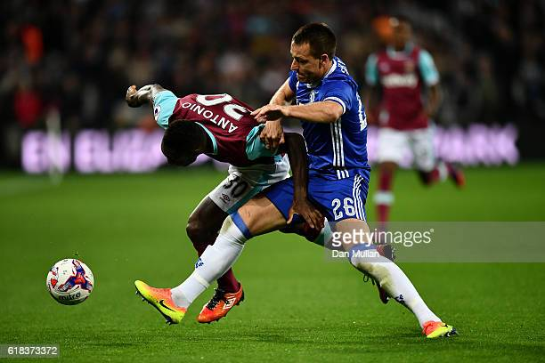 Michail Antonio of West Ham United and John Terry of Chelsea battle for possession during the EFL Cup fourth round match between West Ham United and...