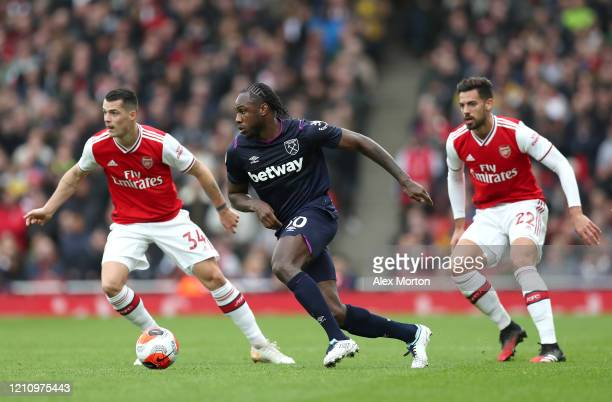 Michail Antonio of West Ham United battles for possession with Granit Xhaka and Pablo Mari of Arsenal during the Premier League match between Arsenal...