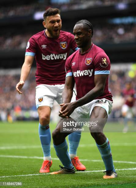 Michail Antonio of West Ham United celebrates with teammate Robert Snodgrass after scoring his team's first goal during the Premier League match...