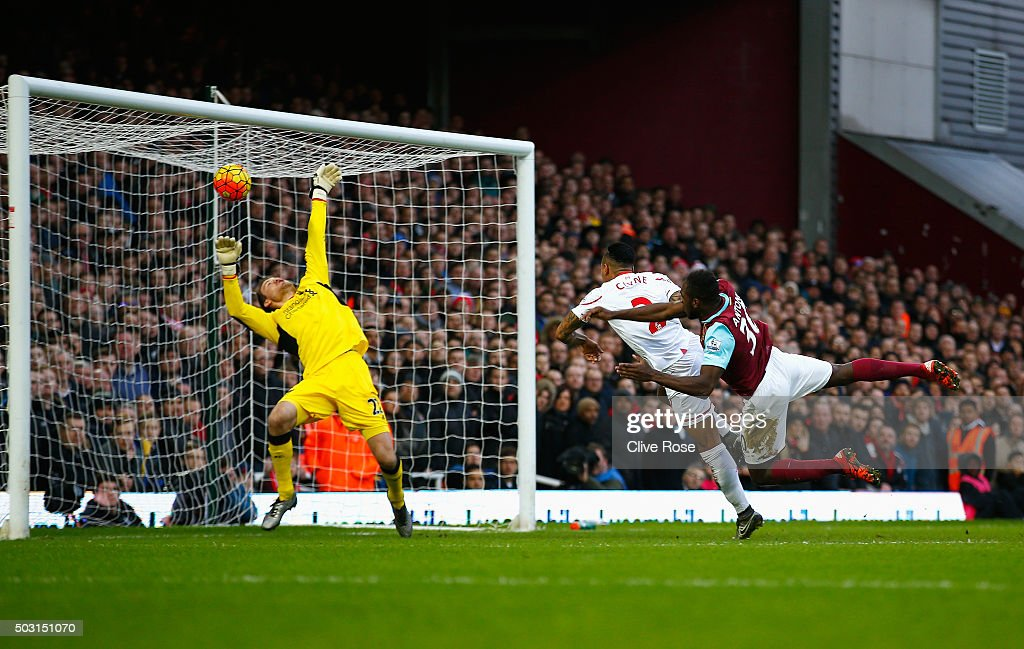 Michail Antonio (R) of West Ham United heads the ball past Simon Mignolet (L) of Liverpool to score his team's first goal during the Barclays Premier League match between West Ham United and Liverpool at Boleyn Ground on January 2, 2016 in London, England.