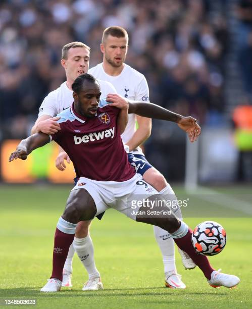 Michail Antonio of West Ham United holds off Oliver Skipp and Eric Dier of Tottenham Hotspur during the Premier League match between West Ham United...