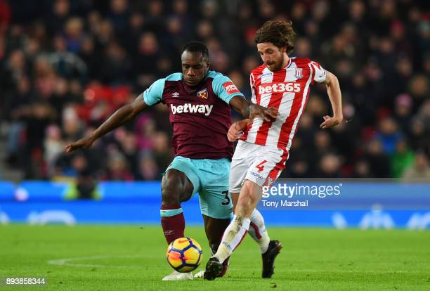 Michail Antonio of West Ham United is challenged by Joe Allen of Stoke City during the Premier League match between Stoke City and West Ham United at...