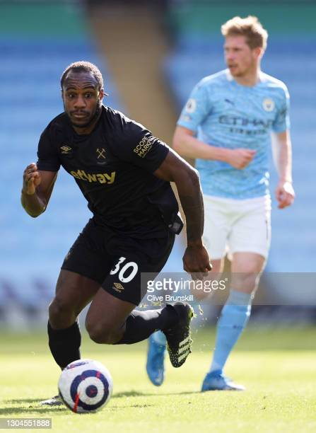 Michail Antonio of West Ham United runs with the ball during the Premier League match between Manchester City and West Ham United at Etihad Stadium...