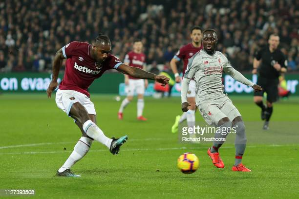 Michail Antonio of West Ham United scores his team's first goal during the Premier League match between West Ham United and Liverpool FC at London...