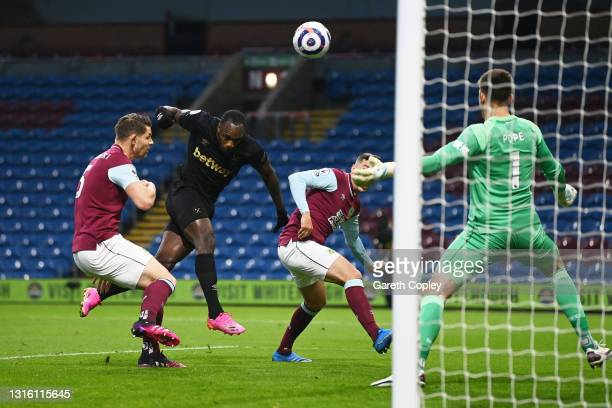 Michail Antonio of West Ham United scores their side's first goal whilst under pressure from James Tarkowski and Matthew Lowton of Burnley during the...