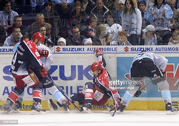 Michail Kozhevnikov and Rene Roethke of Hanover fight for the puck with Vitalij Aab and Greg Classen of Freezers during the DEL Bundesliga match...