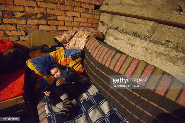 Michal 4yearsold lies on a make shift bed as he and others wait for the end of the shelling in Donetsk's Petrovski district in the eastern Ukraine on...