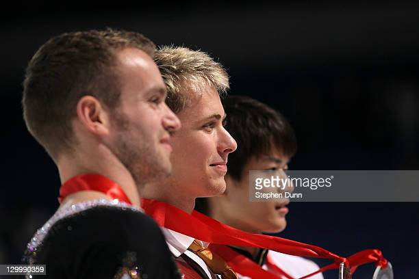 Michal Brezina of the Czech Republic Kevin Van Der Perren of Belgium and Takahiko Kozuka of Japan pose for photos after the men's competition during...
