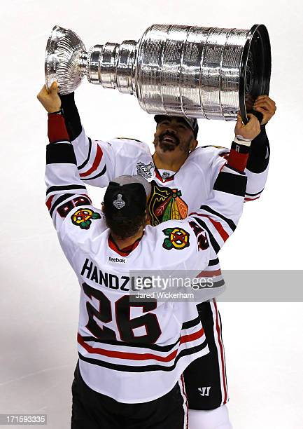 Michal Handzus of the Chicago Blackhawks hands the Stanley Cup to Jamal Mayers after defeating the Boston Bruins in Game Six of the 2013 NHL Stanley...