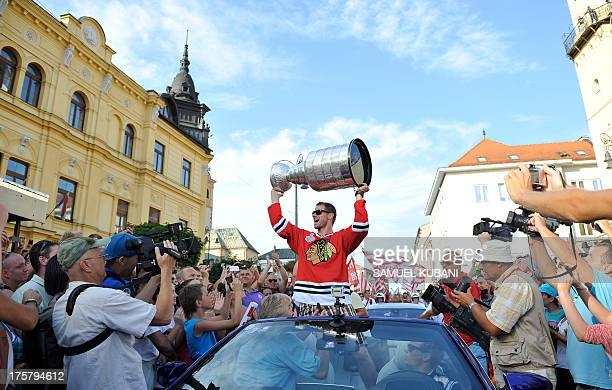 Michal Handzus of the Chicago Blackhawks holds the NHL Stanley Cup as he arrives at main square in Banska Bystrica Slovakia on August 8 2013 during a...