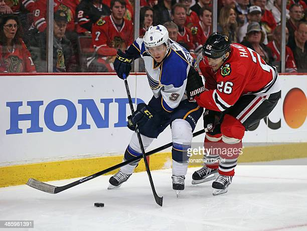 Michal Handzus of the Chicago Blackhawks pokes at the puck through the legs of Jaden Schwartz of the St Louis Blues in Game Three of the First Round...