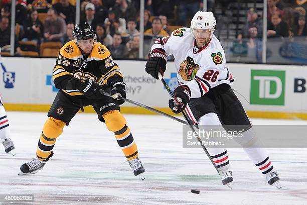 Michal Handzus of the Chicago Blackhawks skates with the puck against Chris Kelly of the Boston Bruins at the TD Garden on March 27 2014 in Boston...