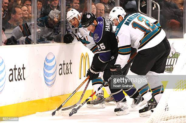 Michal Handzus of the Los Angeles Kings battles for control of the puck between Devin Setoguchi and Patrick Marleau of the San Jose Sharks during...