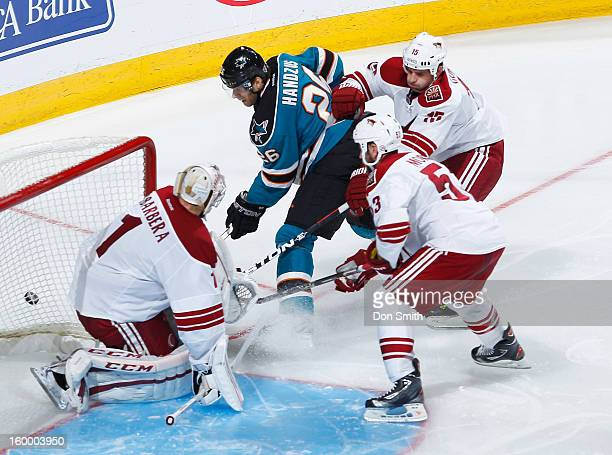 Michal Handzus of the San Jose Sharks crashes the net against Boyd Gordon Derek Morris and Jason LaBarbera of the Phoenix Coyotes during an NHL game...