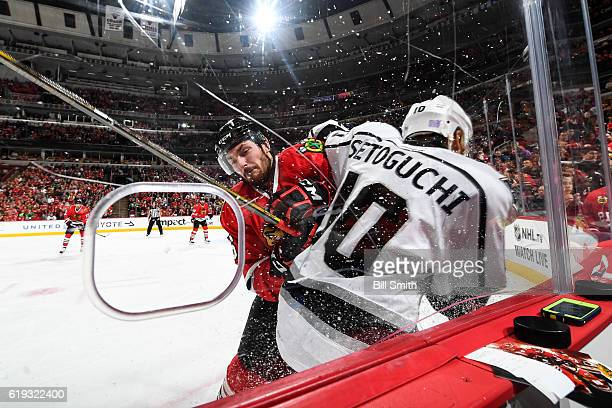 Michal Kempny of the Chicago Blackhawks checks Devin Setoguchi of the Los Angeles Kings into the boards in the second period at the United Center on...