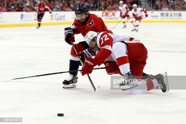 Michal Kempny of the Washington Capitals and Andreas Athanasiou of the Detroit Red Wings go after the puck during the first period at Capital One...