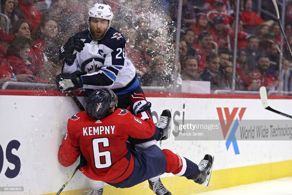 Michal Kempny #6 of the Washington Capitals is checked by Blake Wheeler #26 of the Winnipeg Jets during the third period at Capital One Arena on March 12, 2018 in Washington, DC.