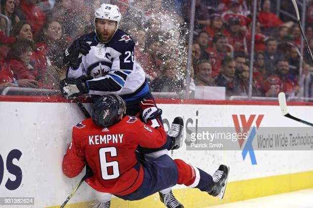 Michal Kempny of the Washington Capitals is checked by Blake Wheeler of the Winnipeg Jets during the third period at Capital One Arena on March 12...