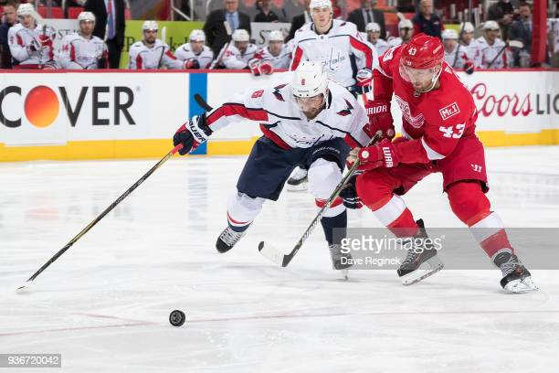 Michal Kempny of the Washington Capitals races after the puck with Darren Helm of the Detroit Red Wings during an NHL game at Little Caesars Arena on...