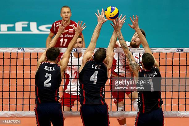 Michal Kubiak of Poland spikes the ball against Aaron Russell David Lee and Matthew Anderson of the Unites States during the FIVB World League Group...