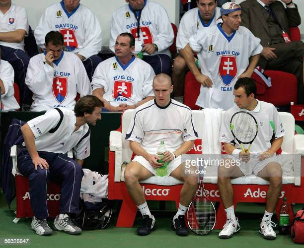 Michal Mertinak and Dominik Hrbaty on the right talk with Team Captain Miloslav Mercir of Slovakia during the doubles against Mario Ancic and Ivan...
