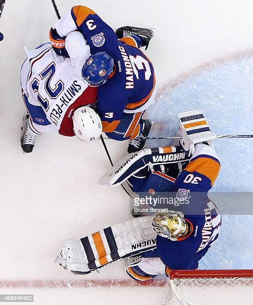 Michal Neuvirth and Travis Hamonic of the New York Islanders combine to stop Devante SmithPelly of the Montreal Canadiens during the second period at...