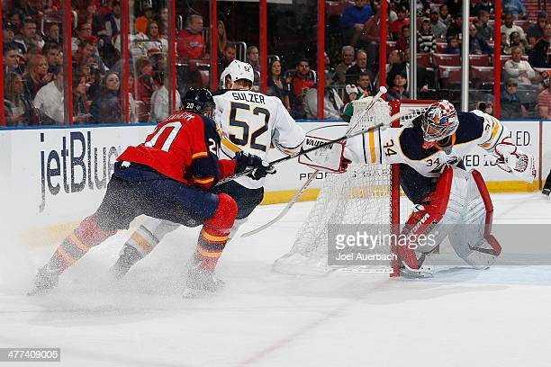 Michal Neuvirth looks back as Alexander Sulzer of the Buffalo Sabres and Sean Bergenheim of the Florida Panthers skate after a loose puck at the BBT...