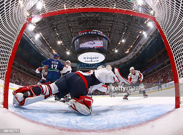 Michal Neuvirth of the Washington Capitals dives to catch the puck on a scoring chance by the Vancouver Canucks during their NHL game at Rogers Arena...