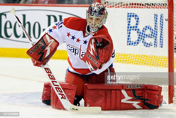 Michal Neuvirth of the Washington Capitals makes a glove save on the puck during the NHL game against the Montreal Canadiens at the Bell Centre on...
