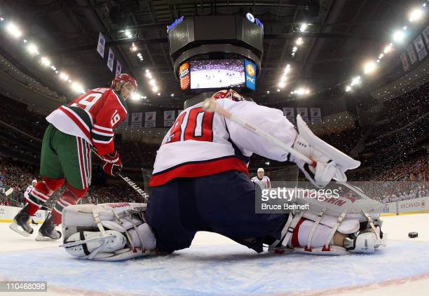 Michal Neuvirth of the Washington Capitals makes the kick save as Travis Zajac of the New Jersey Devils looks for a rebound at the Prudential Center...