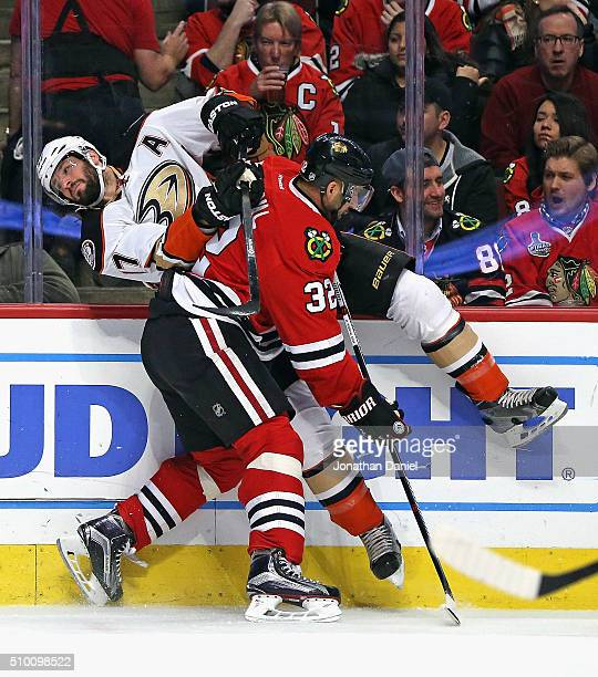 Michal Rozsival of the Chicago Blackhawks checks Ryan Kesler of the Anaheim Ducks into the boards at the United Center on February 13, 2016 in...
