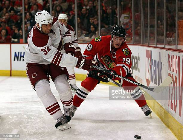 Michal Rozsival of the Phoenix Coyotes and Jonathan Toews of the Chicago Blackhawks battle for the puck at the United Center on February 27 2011 in...