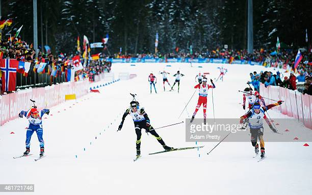 Michal Slesingr of the Czech Republic, Quentin Fillon Maillet of France watch as Simon Schempp of Germany lunges to victory at finish line during the...