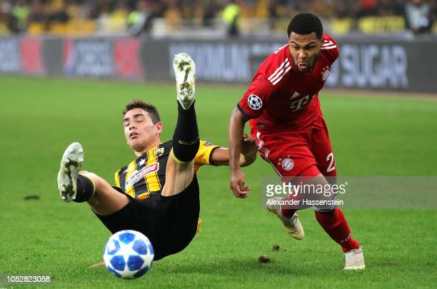 Michalis Bakakis of AEK Athens is challenged by Serge Gnabry of Bayern Munich during the Group E match of the UEFA Champions League between AEK...