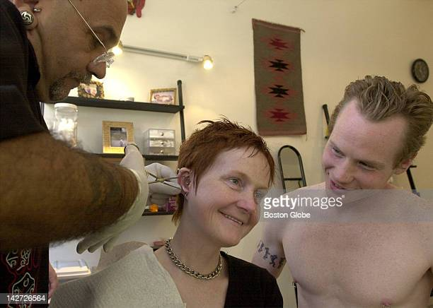 Micheal Desplaines of Tribal Ways Tattoo and Body Piercers gives Melinda Jones a new ear piercing with the support of her husband Tom Clackett as...