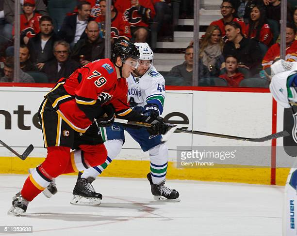 Micheal Ferland of the Calgary Flames battles for the puck against Matt Bartkowski of the Vancouver Canucks at Scotiabank Saddledome on February 19,...