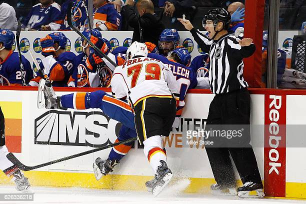 Micheal Ferland of the Calgary Flames checks Adam Pelech of the New York Islanders into the boards at the Barclays Center on November 28, 2016 in...