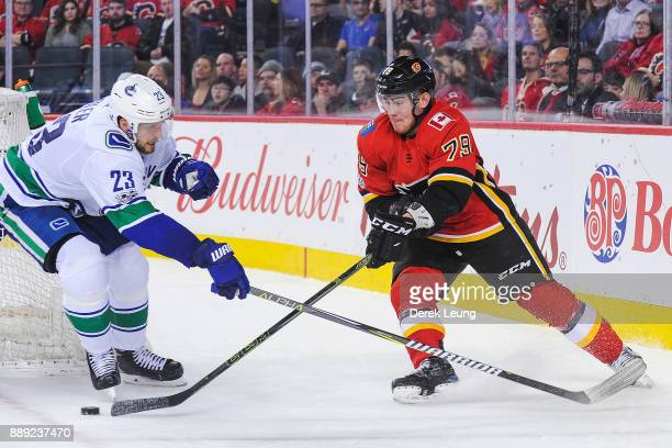 Micheal Ferland of the Calgary Flames fights for the puck against Alexander Edler of the Vancouver Canucks during an NHL game at Scotiabank...