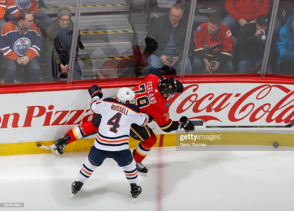 Micheal Ferland #79 of the Calgary Flames protects the puck against Kris Russell #4 of the Edmonton Oilers at Scotiabank Saddledome on March 13, 2018 in Calgary, Alberta, Canada.