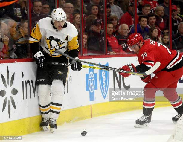 Micheal Ferland of the Carolina Hurricanes and Evgeni Malkin of the Pittsburgh Penguins battle along the boards for the loose puck during an NHL game...
