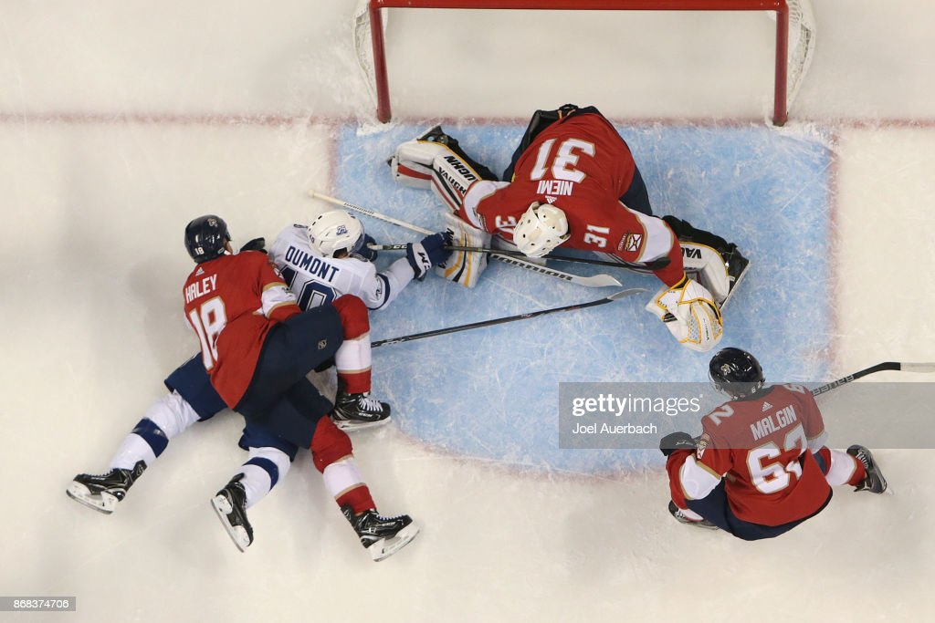 Micheal Haley #18 of the Florida Panthers checks Gabriel Dumont #40 of the Tampa Bay Lightning as Goaltender Antti Niemi #31 stops his shot at the BB&T Center on October 30, 2017 in Sunrise, Florida. The Lightning defeated the Panthers 8-5.