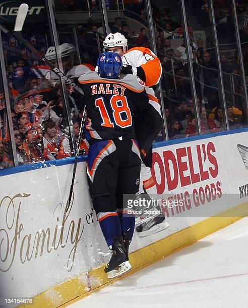 Micheal Haley of the New York Islanders hits Kimmo Timonen of the Philadelphia Flyers at the Nassau Veterans Memorial Coliseum on November 23 2011 in...