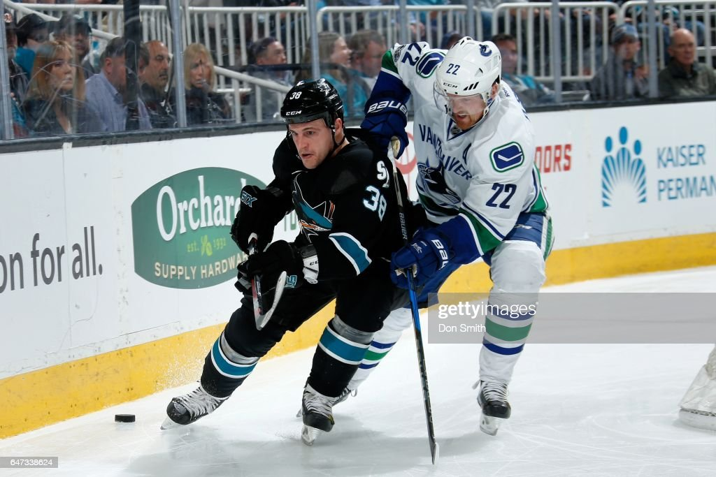 Micheal Haley #38 of the San Jose Sharks and Daniel Sedin #22 of the Vancouver Canucks battle along the boards at SAP Center at San Jose on March 2, 2017 in San Jose, California.