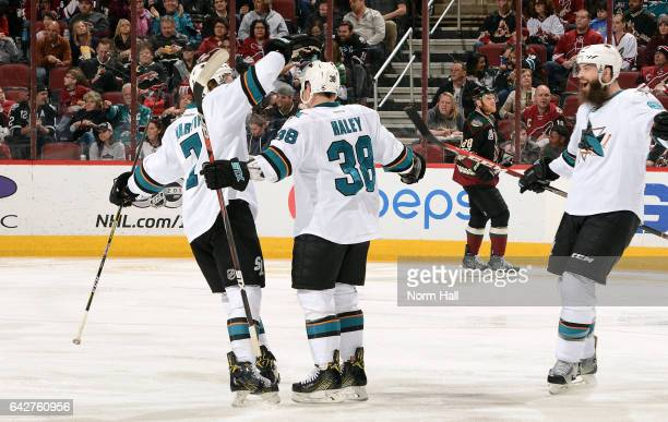 Micheal Haley of the San Jose Sharks celebrates with teammates Paul Martin and Brent Burns after scoring a second period goal against the Arizona...