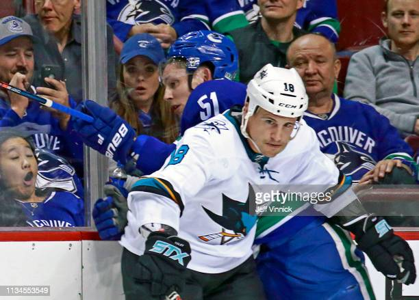 Micheal Haley of the San Jose Sharks checks Troy Stecher of the Vancouver Canucks during their NHL game at Rogers Arena April 2, 2019 in Vancouver,...