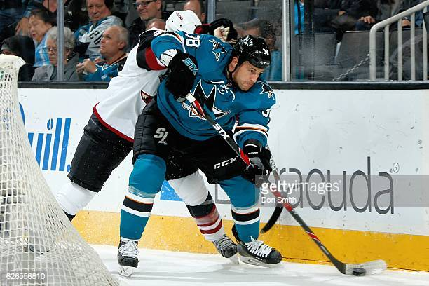 Micheal Haley of the San Jose Sharks is checked while moving the puck during a NHL game against the Arizona Coyotes at SAP Center at San Jose on...