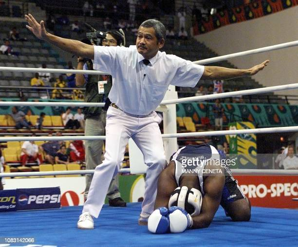 Micheal Macque of Mauritius lies on the canvas on his knees as the boxing referee signals a knock out to the judges during the super heavyweight...